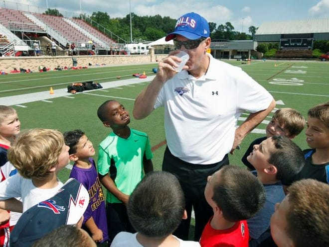 Left in green, CJ Cammack, 9, of Gates and other kids look up at Jim Kelly who takes a sip from a cup at his football camp at St. John Fisher College in Pittsford.