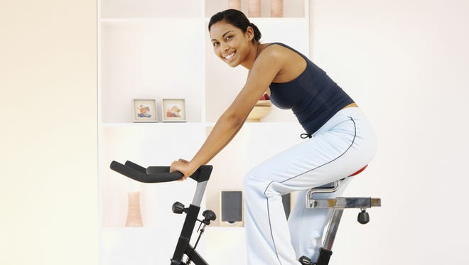 Young woman uses an exercise bike at  home.