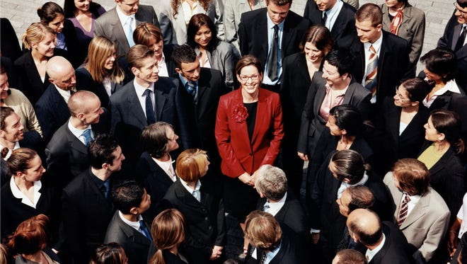 Businesswoman Standing Outdoors Surrounded by a Large Group of Business People