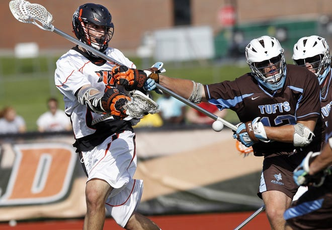 RIT's Eddie Kiesa, left, gets off a one-handed, underhand shot for a goal past Tufts' John Heard.
