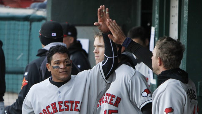 Rochester's Ray Olmedo, left, gets high-fives from teammates on the bench.