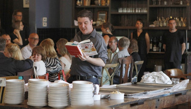 Author Jason Sheehan walks around the large dining area as he reads from his book Cooking Dirty during a special dinner and book club complete with book signing by Rochester native and nationally known food writer Jason Sheehan Monday, May 20, 2013 at Good Luck in Rochester.