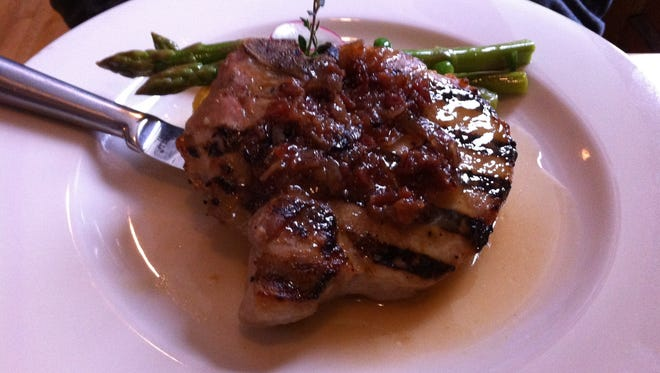 The grilled pork porterhouse consists of a perfectly grilled piece of pork topped with a delicious bacon bourbon marmalade and a light cider-mustard sauce.