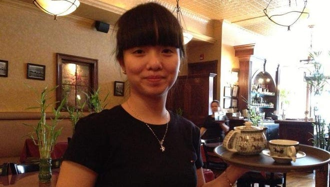 Amy Bai of Happy Family Chinese Restaurant in Seneca Falls serves tea. The eatery offers a unique tea menu and sells Chinese tea sets.