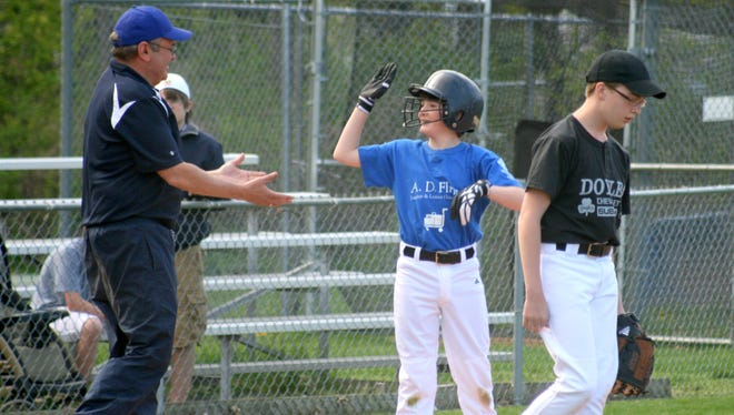 Andy Gagan celebrates with coach Jim Conti after hitting a triple in Pittsford Little League.