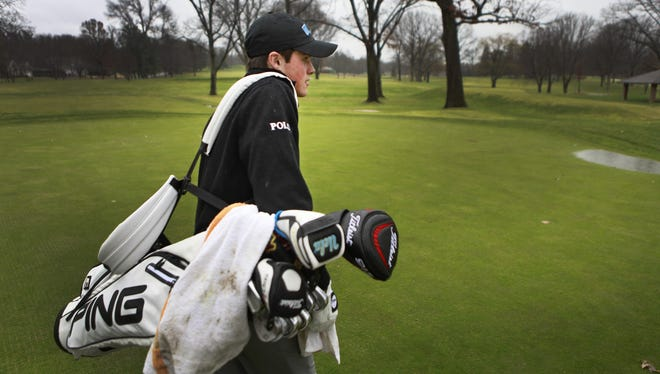 Pittsford Mendon's Gavin Hall  walks out to practice in the rain at Oak Hill CC.  Hall will leave for UCLA on January 4th to start school and his college golf career.