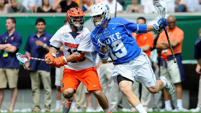 Duke Blue Devils attackman Christian Walsh (19) dodges to the goal around Syracuse Orange midfielder Matt Pratt (10) during the fourth quarter of the 2013 NCAA Division I Men's Lacrosse Championship Game at Lincoln Financial Field.  Duke won the game 16-10.