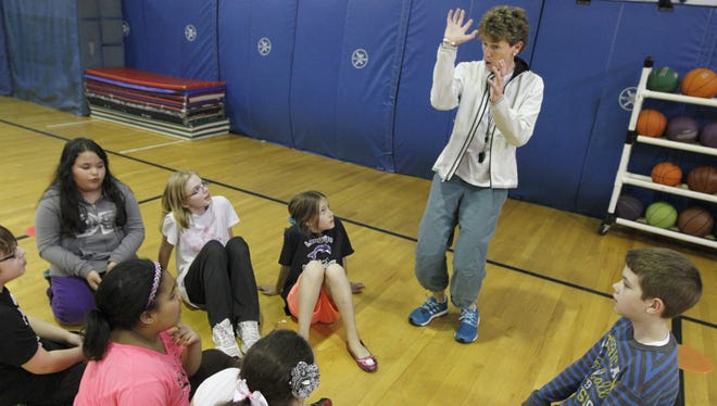 Amy Lembo, a physical education teacher at Longridge Elementary School, guides Laura Brockman's fourth grade class through a lesson on basketball Tuesday, April 30, 2013 in Greece.
