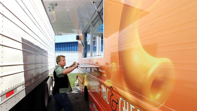 Ian Macdonald, of M Design, examines the shrink wrap decals of  a new mac  and cheese food truck.