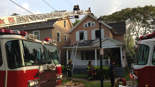Firefighters work at the scene of a fire on Frost Avenue.