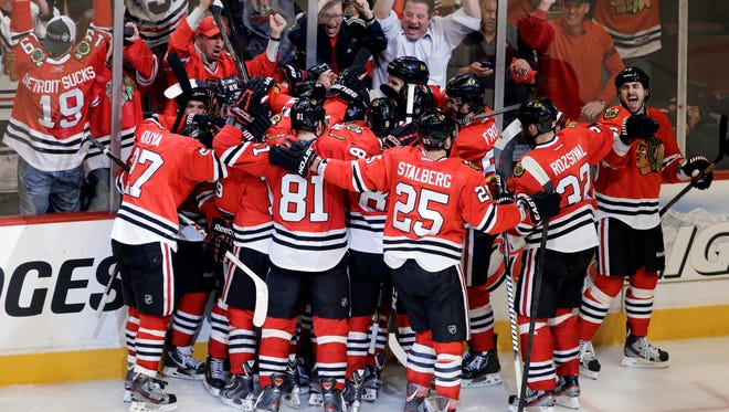 The Chicago Blackhawks celebrate after Brent Seabrook scored in overtime in Game 7 of the NHL hockey Stanley Cup Western Conference semifinals against the Detroit Red Wings.