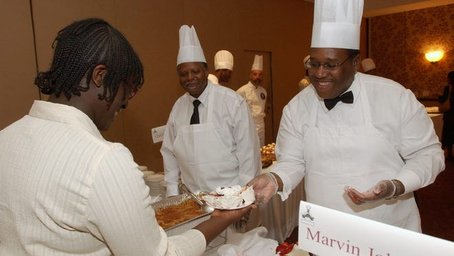 Marvin Johnson, right, serves Meghan Cornwall his Strawberry Summertime cake during the Rochester Urban League Distinguished Male Cooks event in 2006.