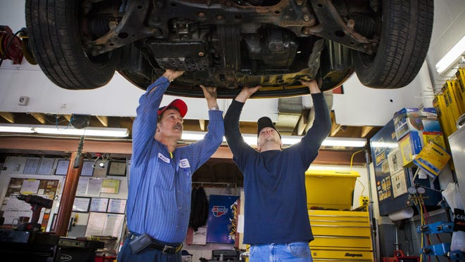 Andre'a Mercone, 28, and his father Andrea, work on an sports utility vehicle at their auto repair shop located on Lake Avenue. Andrea's Auto Shop, located near the Eastman Business Park, has been in business since 1991.