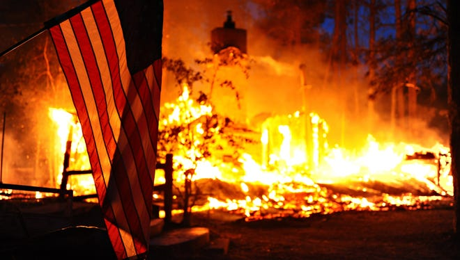 An American flag hangs in front of a burning structure in the Black Forest, a thickly wooded rural region north of Colorado Springs, Colo. Authorities reported early Saturday that 473 houses had been incinerated.