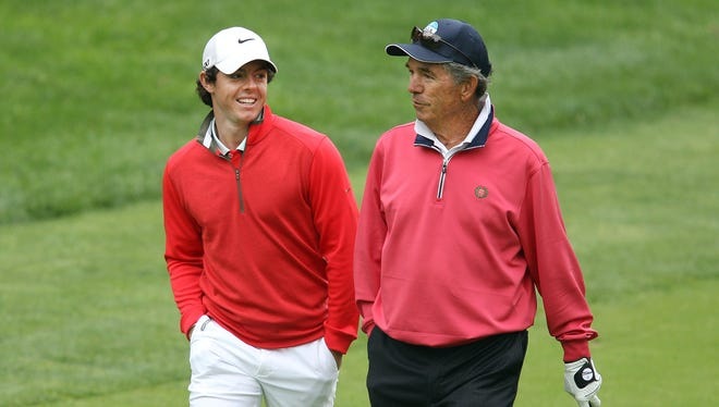 Rory McIlroy and Oak Hill club pro Craig Harmon walk together on the second fairway.