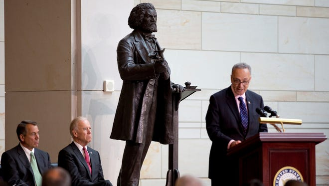 Sen. Charles Schumer, D-N.Y., speaks at right as House Speaker John Boehner of Ohio and Vice President Joe Biden sit left, during a ceremony to dedicate the statue of Frederick Douglass in Washington.