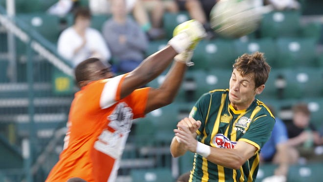 The Rhinos' Blake Brettschneider, right, collides with Antigua goalkeeper Molvin James as James punches out a shot during USL soccer action between the Antigua Barracuda FC and the Rochester Rhinos at Sahlen's Stadium on Friday, June 21, 2013. Rochester won the match 2-1.
