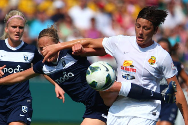 Seattle Reign's defender Elli Reed battles for the ball against Flash's forward Abby Wambach.