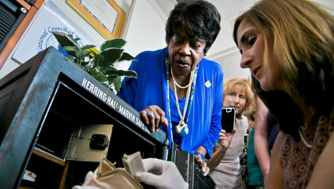 Mary E. Singletary, left, president of the National Council of Women of the U.S., observes as Catherine Carulli, right, director for the University of Rochester Susan B. Anthony Center, examines the contents of a safe on Tuesday in New York.