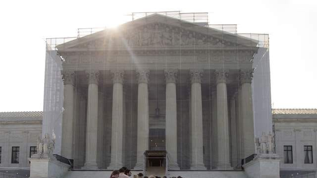 People wait outside the Supreme Court on Monday in Washington.