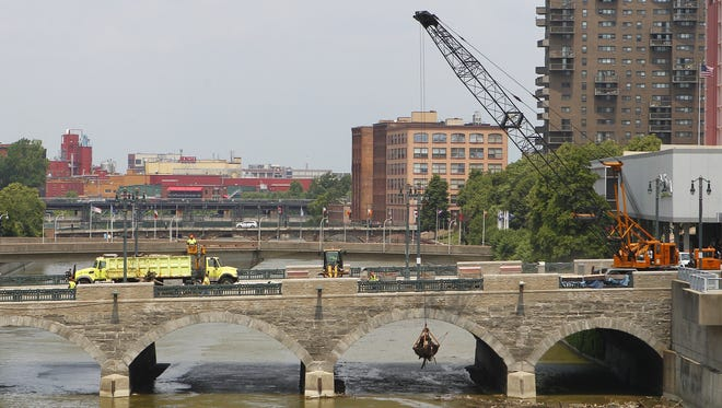 Crews clear logs and debris from the Genesee river under and around the Main Street bridge Sunday afternoon, June 23, 2013.