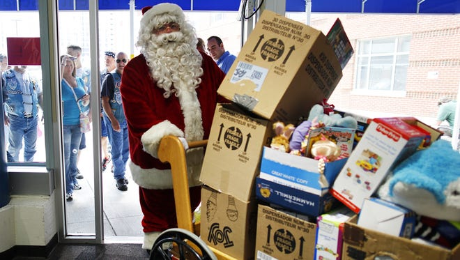 Patrick Andrews of Williamson, dressed as Santa Claus, delivers boxes filled with toys accompanied by the Blue Knights International Law Enforcement Motorcycle Club, Sunday, July 7, 2013. The toys are to benefit the Golisano Children's Hospitals young patients. Andrews's daughter died at the young age of 13, which is what inspired Andrews to give other patients at the hospital a little happiness.