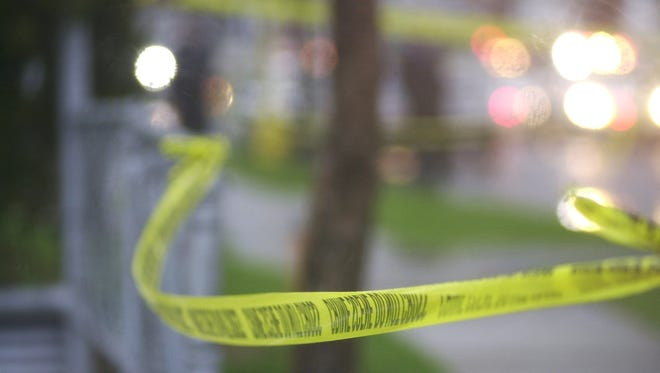 Crime tape blows in the wind at a crime scene.