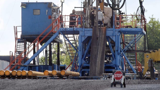A crew works on a gas drilling rig at a well site for shale-based natural gas in Zelienople, Pa., in 2012.