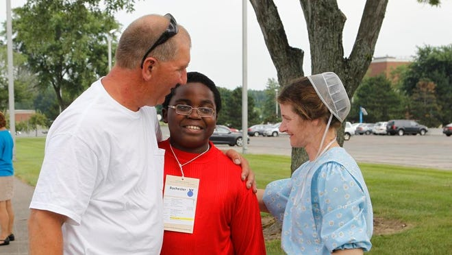 Kareem Carey, 11, of Brooklyn, center, gets hugs from his fresh air family, Wilmer and Sherri Horst, of Sodus, during the Fresh Air program drop off at MCC in Brighton Thursday afternoon, July 18, 2013. Carey, who stayed his the Horst family last year, said the two things he's most excited to do is milk the cows and go to the beach.