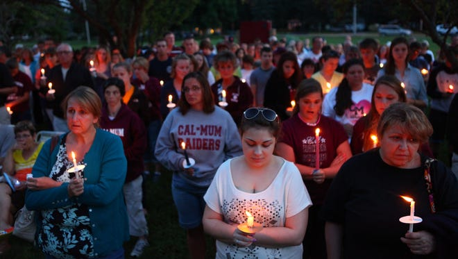 Ashley Toland, center, played soccer with Emily Peterson when the two were children. Toland gathered with a group in Caledonia Sunday for a candlelight vigil to remember Petserson and two others killed in a crash last week.