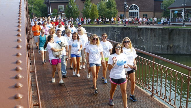 A group of walkers cross the canal bridge in Fairport last year during the the annual Fairport Angels Walk.
