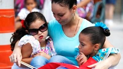 Lisa Martinez, center, shares a moment with Harley Bermudez, 4, and Emani Torres, 4, all of Rochester, during the Rochester Puerto Rican Parade.