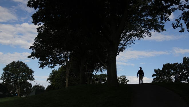 A volunteer stands at the top of the hill on 13.
