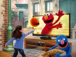 "Kids pretend to throw Paul the Ball, a new Sesame Street character, when playing """"Kinect Sesame Street TV,"" a new interactive TV game from Microsoft Studios."