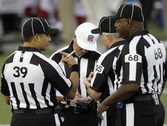 Referee Craig Ochoa, center, meets with other replacement officials before the Hall of Fame preseason game between the Cardinals and  Saints on  Aug. 5 in Canton, Ohio.