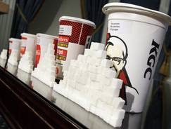 The consumption of sugary drinks can increase the genetic risk of obesity in some people, a study finds.