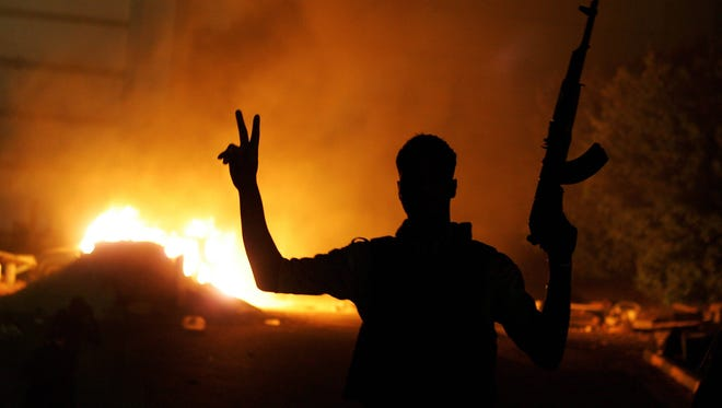 An armed Libyan man flashes the victory sign in front of a fire at the hardline Islamist group Ansar el-Sharia headquarters last year.