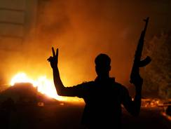 An armed Libyan man flashes the victory sign in front of a fire at the hardline Islamist group Ansar el-Sharia headquarters on Friday in Benghazi. Hundreds of Libyan protesters forced members of a hardline Islamist militia out of their base, setting fire to and wrecking the compound.