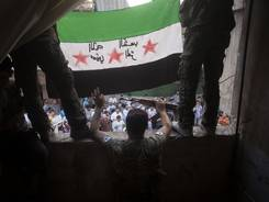 Free Syrian Army rebels hold a revolutionary flag during Friday's demonstration in Aleppo, Syria.