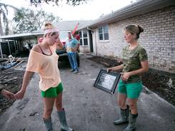 Suzanne Shaffer, right, shows her daughter Amanda Shaffer a photo of Katrina damage to their home. Their Braithwaite, La., home was also flooded by waters from Isaac.