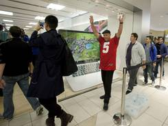 Paul Lewis, of Zionsville, Ind. celebrates after the Apple Store opens in the Keystone at the Crossing Mall in Indianapolis early Sept. 21, 2012, where people lined up overnight to purchase the iPhone 5.