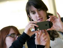 Customers look over an Apple iPhone 5 at a store in San Francisco on Friday.
