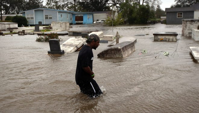 Errol Ragas walks past a cemetery to recover blankets from his home as rising waters from Hurricane Isaac flood his neighborhood Aug. 29 in Plaquemines Parish, La.