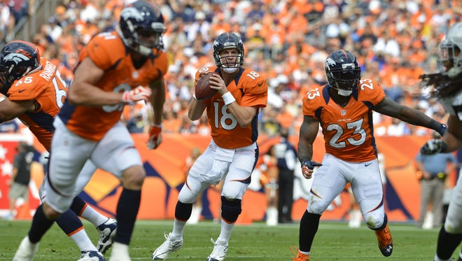 Denver Broncos quarterback Peyton Manning completed 30 of 38 passes for 338 yards and three touchdowns in a 37-7 blowout of the Oakland Raiders.