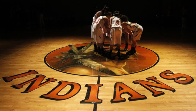The Mohawk High School girls basketball team meeting at mid-court on a painting of their school mascot in Marcola, Ore.