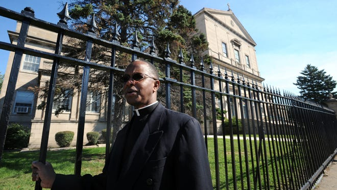 The Rev. Mark Kalema stands outside Our Lady of Peace Catholic Church in Chicago. There have been numerous shootings and other crimes right outside the church, which is located in the city's troubled South Shore neighborhood.