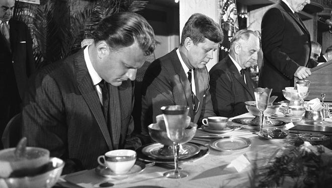 The Rev. Billy Graham and President John F. Kennedy bow their heads in prayer in 1961, although at that time the Catholic Church did not permit Catholics and Protestants to pray together.