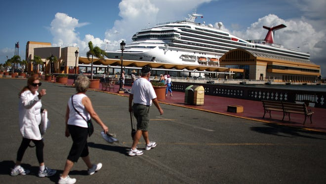 Tourists walk through a parking lot in front of a pier Oct. 2 where a cruise ship is docked in Old San Juan, Puerto Rico.