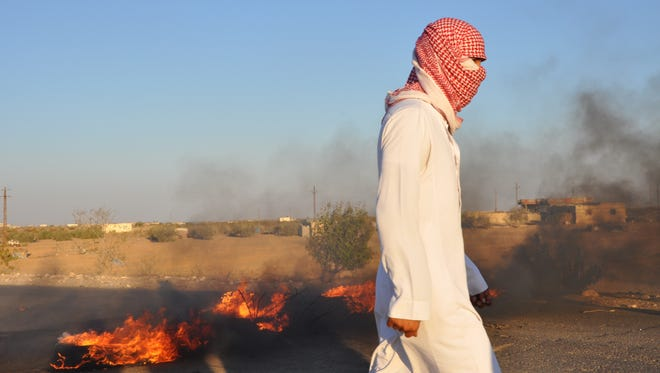 A resident of North Sinai walks past burning tires on a desert road.