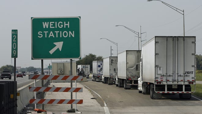 Drivers move their trucks in single file to a weigh station maintained by Texas Department of Public Safety troopers on Interstate 35.